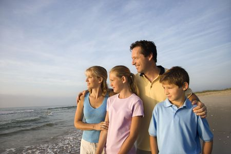 Portrait of Caucasian family of four posing on beach looking at ocean. photo