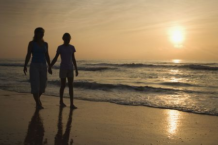 prime adult: Caucasian prime adult female and female child walking on beach at sunset holding hands.