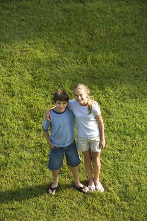 preteen boy: Du Caucase pr�-adolescent gar�on et une fille debout sur la pelouse avec des armes autour de l'autre.