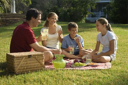 bald head island: Caucasian family of four having picnic in park. Stock Photo