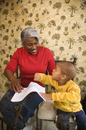 Portrait of African American grandmother with grandson coloring.