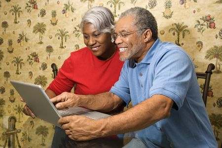 Portrait of mature African American couple looking and smiling at laptop in home.  photo
