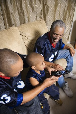 Three male generations of an African-American family watching football game on tv with boy holding remote. photo