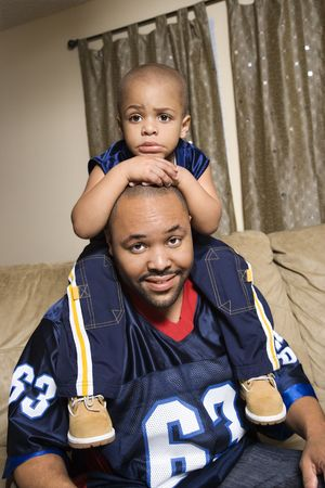 Portrait of African-American father with his son on his shoulders. photo
