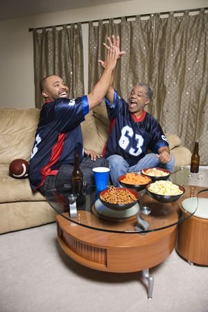 den: African-American father and son giving high five while watching football game. Stock Photo