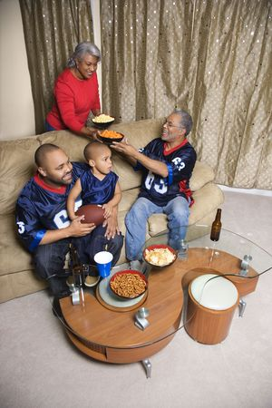 Mother serving snacks to male African-American family members during football game.  Stock Photo