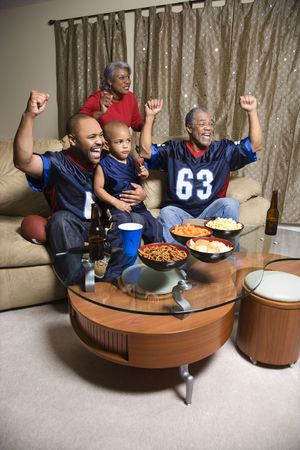 family sofa: A three generation African-American family cheering and watching football game together on tv.