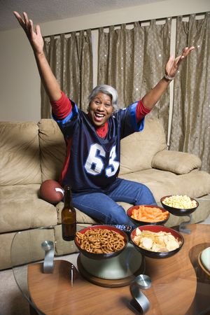 Portrait of a Middle-aged African-American woman wearing a football jersey with hands in the air watching football game.  photo