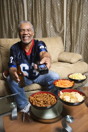Portrait of a Middle-aged African-American man wearing a football jersey surrounded by snacks pointing a remote at viewer. photo