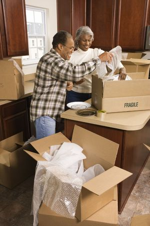 Middle-aged African-American couple packing moving boxes in kitchen. photo