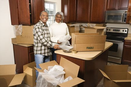 Portrait of middle-aged African-American couple packing moving boxes in kitchen. photo