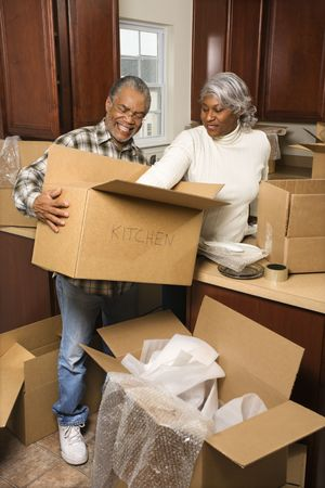 Portrait of middle-aged African-American couple packing moving boxes in kitchen. Stock Photo - 1797444