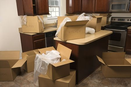 unpacking: Cardboard moving boxes with bubble wrap in kitchen. Stock Photo