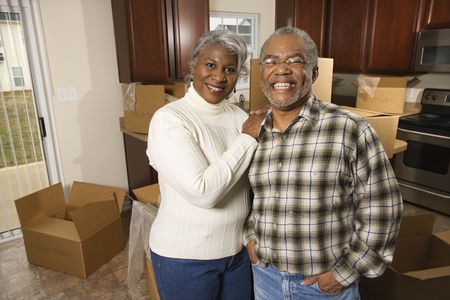Portrait of middle-aged African-American couple in kitchen with moving boxes. photo