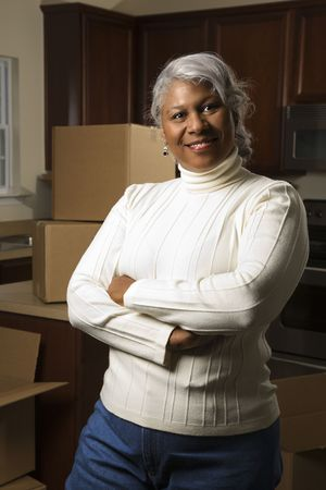 Portrait of middle-aged African-American female in kitchen with moving boxes. Stock Photo - 1795576