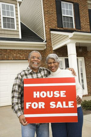 Portrait of middle-aged African-American couple outside house with for sale sign. photo