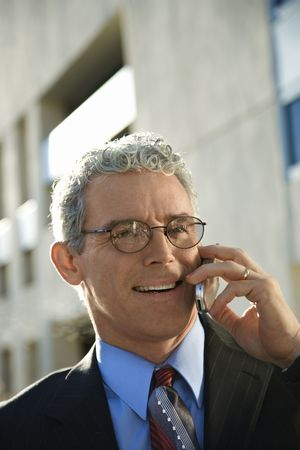 prime adult: Prime adult Caucasian man in suit smiling and talking on cellphone in urban setting.