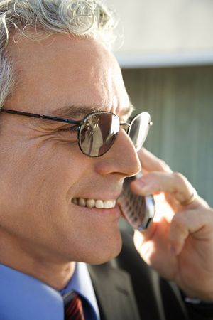 prime adult: Close up profile of prime adult Caucasian man in suit smiling and talking on cellphone in urban setting.
