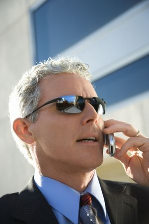 Close up side view of prime adult Caucasian man in suit talking on cellphone in urban setting.