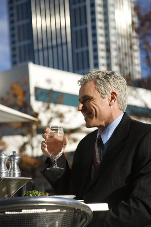 prime adult: Prime adult Caucasian man in suit sitting outside drinking water at patio table in urban setting. Stock Photo