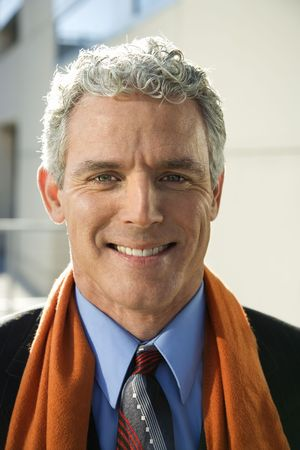 Close up of prime adult Caucasian man in suit looking at viewer smiling.