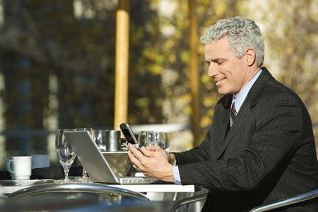 Profile of smiling prime adult Caucasian man in suit sitting at patio table outside with laptop and dialing cellphone. photo