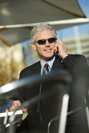 Prime adult Caucasian man in suit sitting at ouside patio table wearing sunglasses and talking on cellphone smiling. Stock Photo