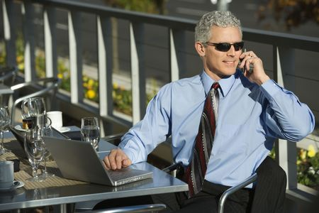 prime adult: Prime adult Caucasian man in suit sitting at patio table ouside with laptop and talking on cellphone.