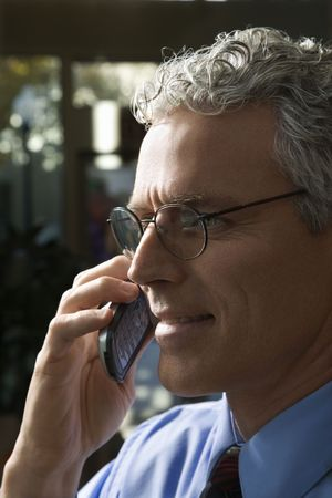 prime adult: Close up profile of prime adult Caucasian man in suit talking on cellphone.