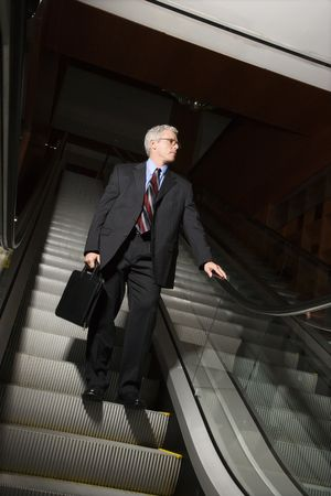 Prime adult Caucasian man in suit holding briefcase standing on down escalator holding rail. photo