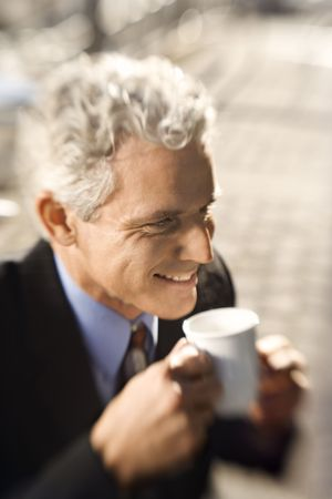 prime adult: Selective focus close up of prime adult Caucasian man in suit drinking coffee and smiling.