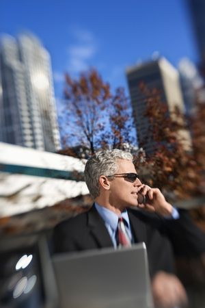 prime adult: Prime adult Caucasian man in suit sitting at patio table outside with laptop talking on cellphone wearing sunglasses with buildings in background.