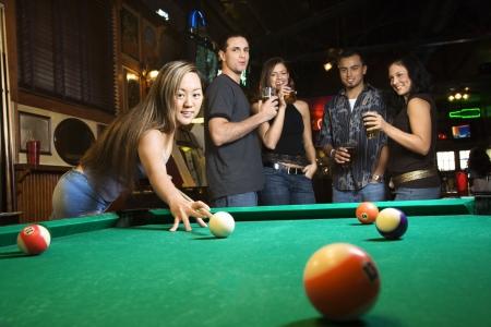 hombre tomando cerveza: Young asian mujer golpe� a la preparaci�n de la piscina de bolas mientras juega al billar.