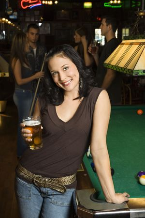 one person with others: Portrait of young caucasian woman holding beer beside billiards table in pub. Stock Photo