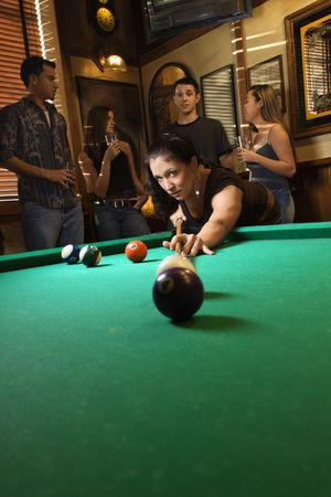 one person with others: Young caucasian woman preparing to hit pool ball while playing billiards. Stock Photo