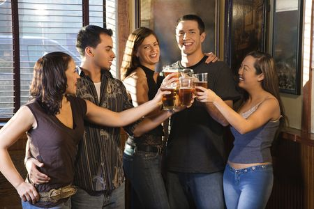Group of young friends hanging out in pub and toasting with their beers. photo