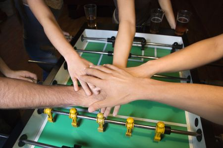 clasping: Group of young friends clasping hands in solidarity over foosball table.