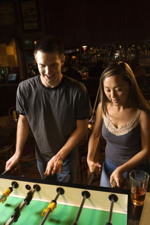 Young couple teamed up at foosball game in pub. Stock Photo