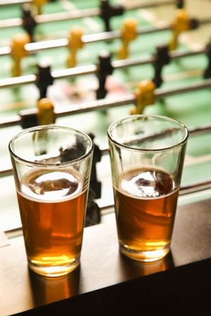 Two glasses of beer on foosball table. Stock Photo