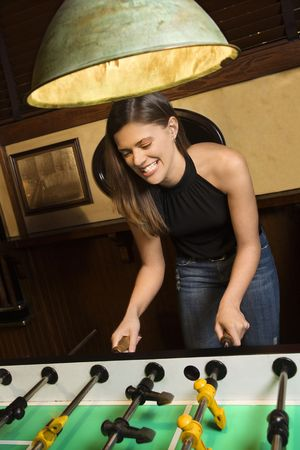 Young woman smiling while playing foosball game at pub. Stock Photo - 1795598