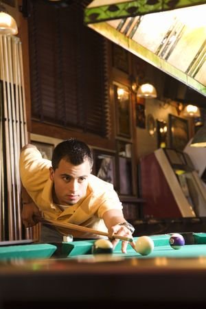 concentrating: Young man concentrating while aiming at pool ball while playing billiards.