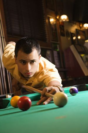 pool ball: Young man concentrating while aiming at pool ball while playing billiards.