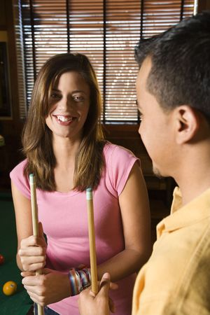 Young man and woman talking and smiling while playing billiards. Stock Photo - 1798643