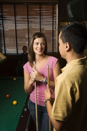 two people with others: Young man and woman talking and smiling while playing billiards.