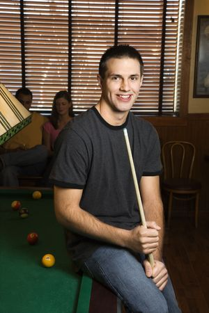 one person with others: Portrait of young man leaning on billiards table holding pool stick.