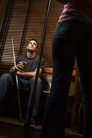 one person with others: Young man with billiards cue looking at woman standing before him. Stock Photo