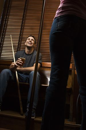 Young man with billiards cue talking with woman standing before him. photo
