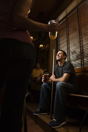 Young man holding billiards cue while hanging out at pub. photo