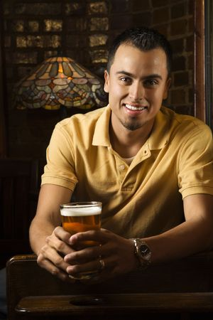 Portrait of smiling young Hispanic man holding beer in pub. Stock Photo - 1798633