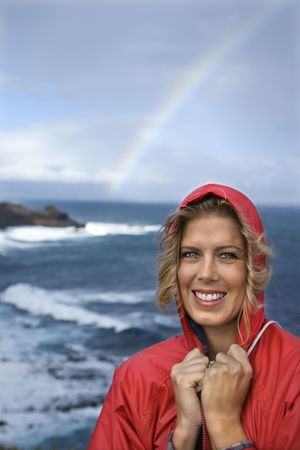 Caucasian mid-adult woman in red raincoat standing by ocean with rainbow in background in Maui, Hawaii. photo
